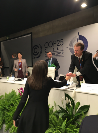 UN Special Rapporteur map of countries recognizing healthy environment as a human right shaking hands with the queen of spain at COP 25