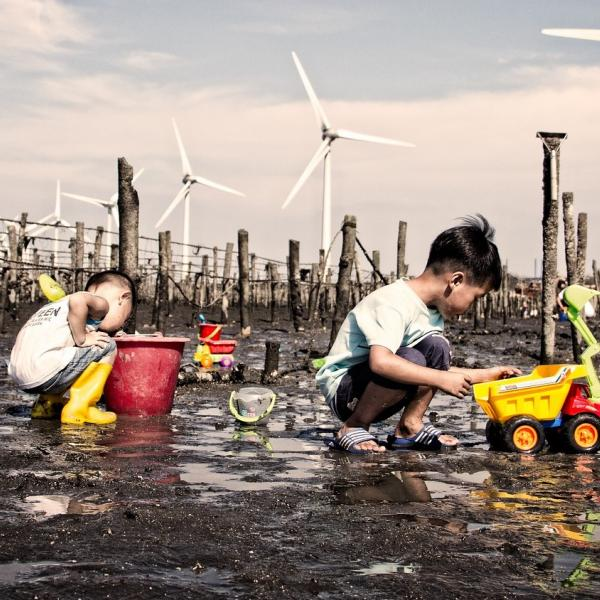 kids playing in the mud in front of wind turbines